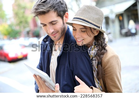 Couple in town connected on digital tablet