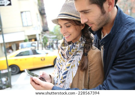 Couple in town using smartphone - stock photo