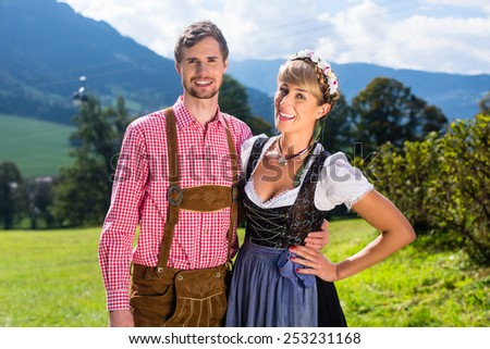 Couple in Tracht standing on meadow in alp mountains, a cable car is running in the background - stock photo