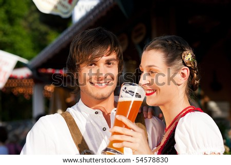 Couple in traditional Bavarian Tracht - Dirndl and Lederhosen - in front of a beer tent at the Oktoberfest or in a beer garden enjoying a glass of tasty wheat beer