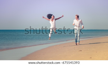 Couple in vacation on beach, black woman and white man