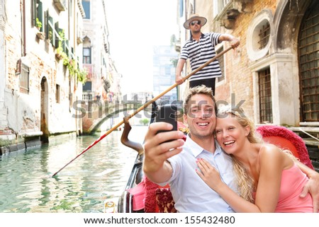 Couple in Venice on Gondole ride romance in boat happy together on travel vacation holidays. Romantic young beautiful couple taking self-portrait sailing in venetian canal in gondola. Italy. - stock photo