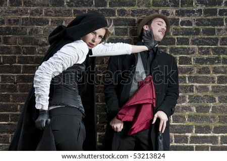 Couple in victorian costumes, woman strangling man. - stock photo