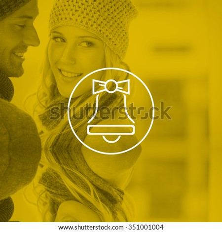 Couple in warm clothing hugging against christmas bell - stock photo
