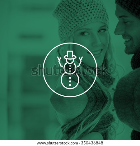 Couple in warm clothing hugging against snowman - stock photo