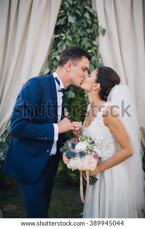 couple in wedding attire exchange rings with a bouquet of flowers and greenery in the garden with arch on background, the bride and groom - stock photo