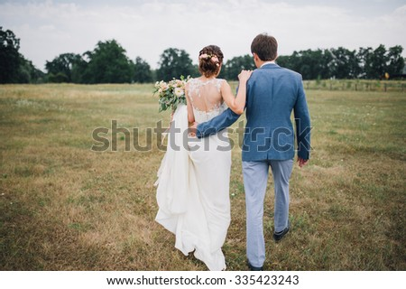 couple in wedding attire is standing on a green field on the background of the forest, the bride and groom