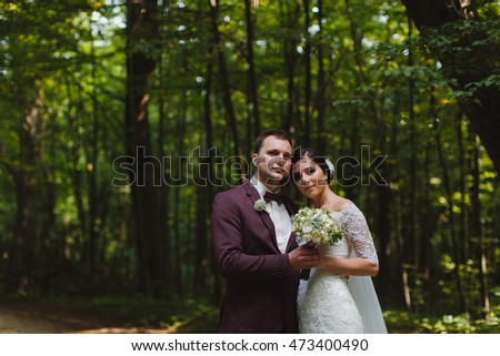 couple in wedding attire with a bouquet of flowers and greenery