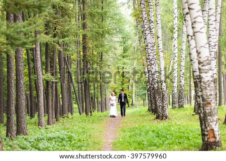 couple in wedding attire with a bouquet of flowers, bride and groom outdoors