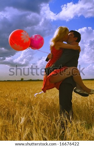 Couple in wheat fields kissing - stock photo