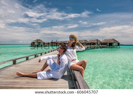 Couple in white on a tropical beach jetty at Maldives