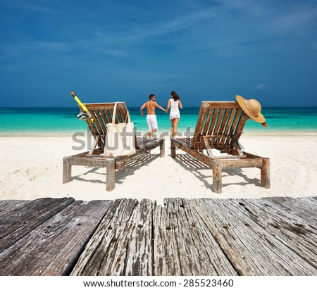 Couple in white relax on a tropical beach at Maldives - stock photo