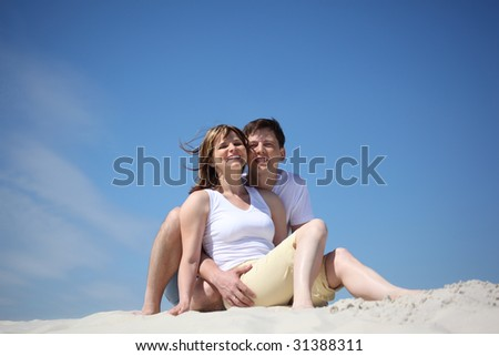 couple in white shirts sitting on sand