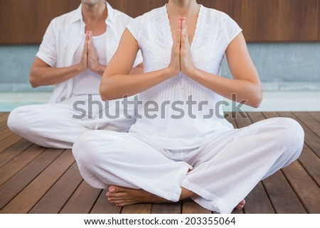 Couple in white sitting in lotus pose with hands together in health spa - stock photo