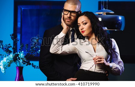 Couple indoors. Sensual brunette and handsome businessman hugging. Office romance concept - stock photo