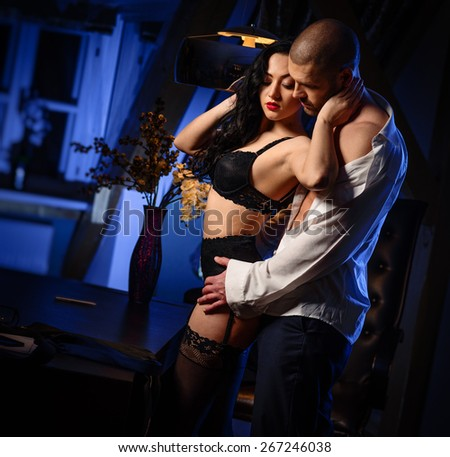 Couple indoors. Sensual brunette in black lingerie and handsome man. Office romance concept  - stock photo