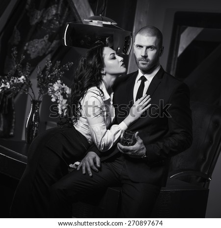 Couple indoors. Sensual brunette seduces handsome businessman. Office romance concept
