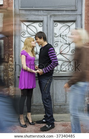 Couple inlove standing on the street, other people in motion. - stock photo