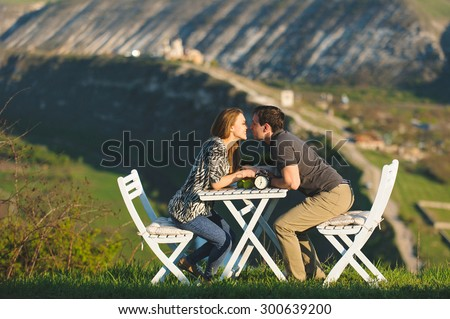 couple is going to kiss sitting at table - stock photo