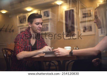 Couple is having a date in a cafe. They drink coffee tea and talk to each other - stock photo
