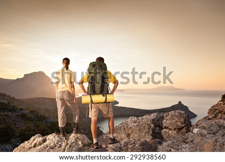 Couple is hiking a mountain and looking at the sea - stock photo