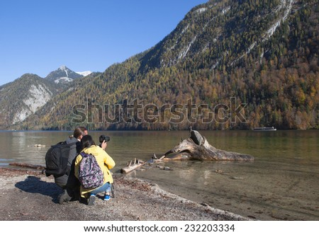 Couple is taking a picture of a trunk in the water.Picture is made on a sunny autumn day .The driftwood is laying near the riverside. - stock photo