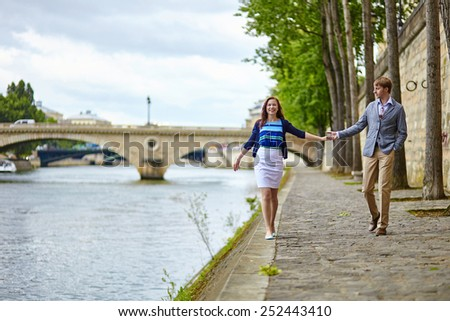 Couple is walking by the Seine embankment in Paris - stock photo