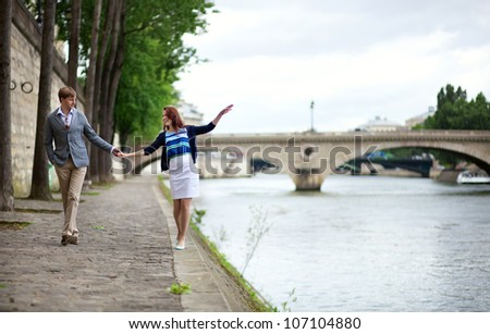 Couple is walking by the Seine embankment in Paris, girl is balancing on the water edge - stock photo
