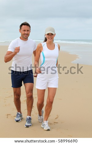 Couple jogging on a sandy beach - stock photo