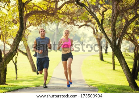 Couple jogging running outside in the park at sunrise on beautiful path. Healthy lifestyle fitness concept.  - stock photo