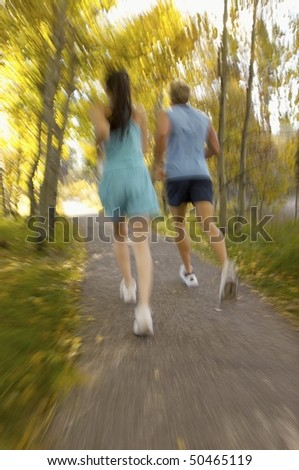 Couple jogging through woods, rear view