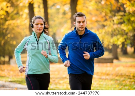 Couple jogging together in nature, woman listening music - stock photo