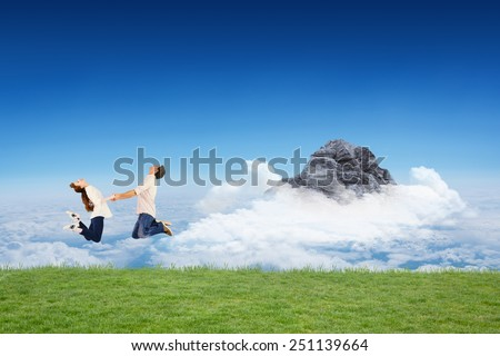 Couple jumping and holding hands against mountain peak through the clouds - stock photo