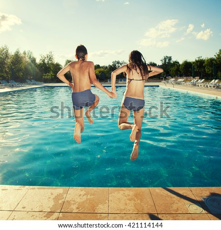 Couple jumping into pool outdoors. Summer vacations