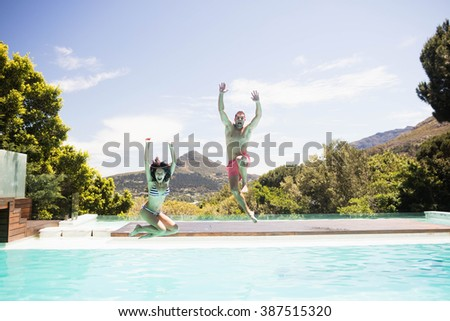 Couple jumping into swimming pool with their hand raised - stock photo