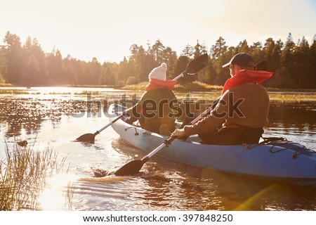 Couple kayaking on lake, back view, close-up - stock photo