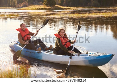 Couple kayaking on lake, front view, Big Bear, California - stock photo