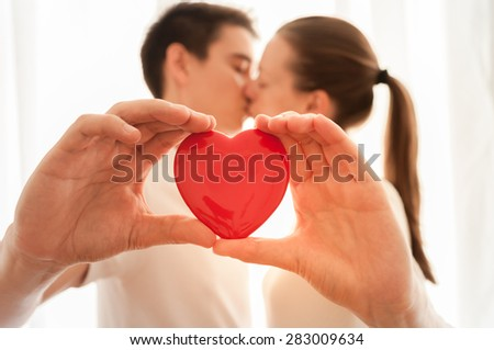Couple kissing and holding heart. - stock photo