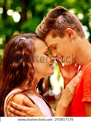 Couple kissing and relate to each other's noses at park. Outdoor. - stock photo