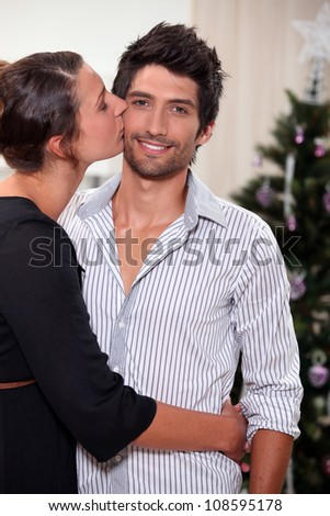 Couple kissing at Christmas - stock photo