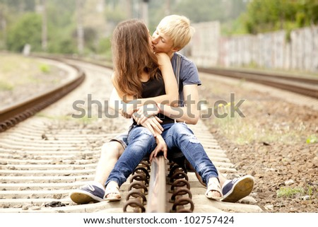 Couple kissing at railway. Urban photo. - stock photo