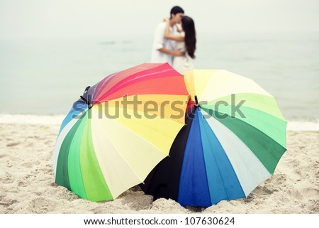 Couple kissing at the beach and umbrella - stock photo
