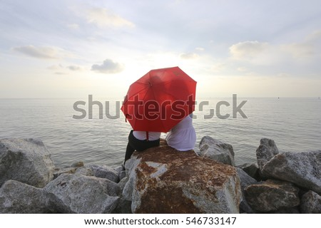 Couple kissing behind umbrella while facing sea during sunset