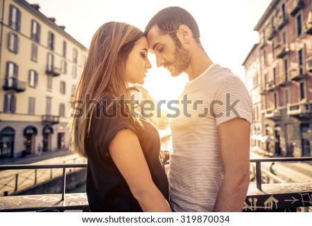 couple kissing each other on a bridge over the river. concept about passion and love - stock photo