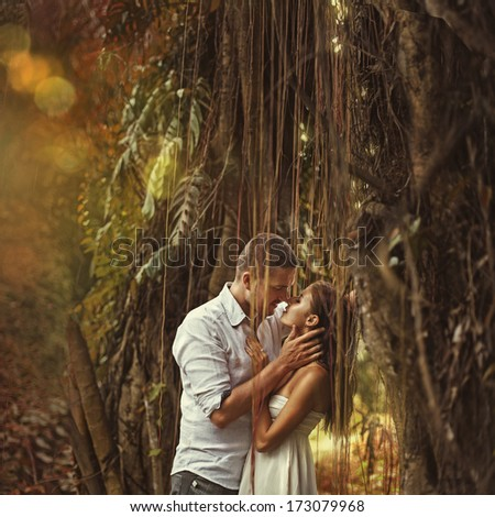 couple kissing in mysterious forest (bali, indonesia) - stock photo