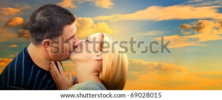 Couple kissing in romantic love scenery on sunset sky. Panorama version - stock photo