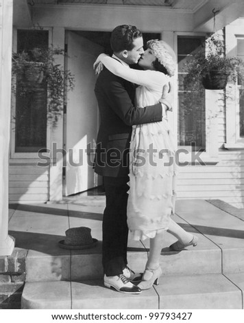 Couple kissing on front porch