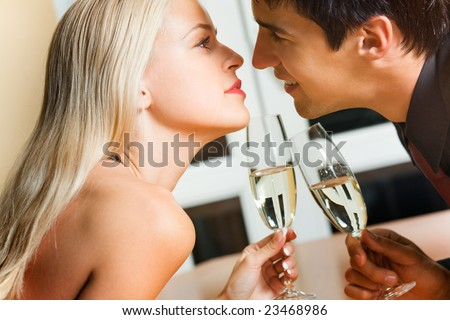 Couple kissing on romantic date or celebrating together at restaurant - stock photo