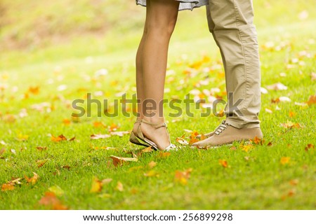 couple kissing outdoors at the park - stock photo