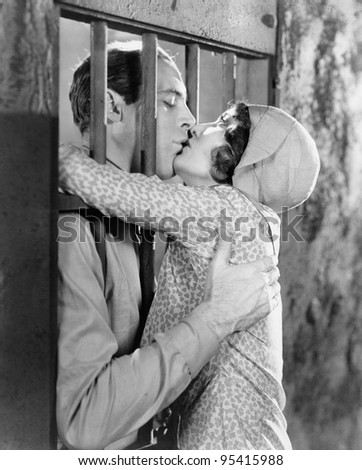 Couple kissing through bars of jail cell - stock photo